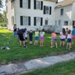 LCHS Museum Manager Allyson Earl explains the rules of croquet to a group of students on a field trip to the Swetland Homestead.